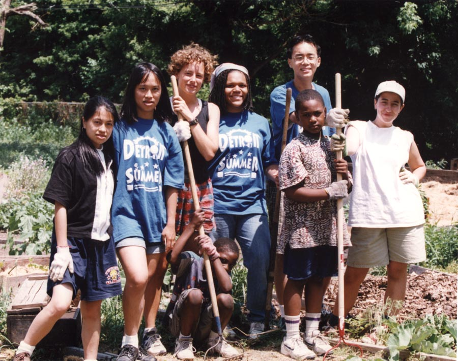 8 youth from Detroit Summer posing for a photo, in a garden holding garden tools